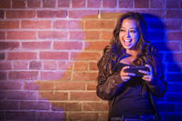 Mixed Race Woman Using Her Cell Phone Against Brick Wall