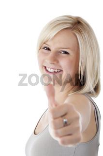 Attraktive blonde Frau hält lächelnd Daumen nach oben