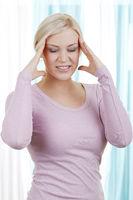 Blonde Frau mit Kopfschmerzen