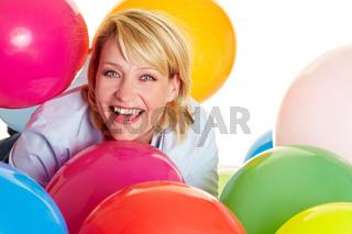 Frau inmitten bunter Ballons