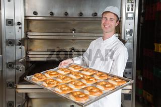 Bäcker mit einem Backblech voller frischer Brezeln