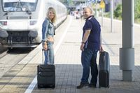 Couple with suitcase on the platform