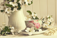 Tea cup with fresh apple blossoms on table