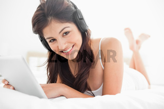Woman with a tablet and headphones looking forward and smiling