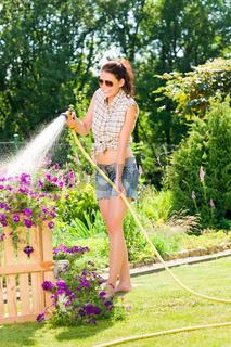 Summer garden smiling woman watering hose flower