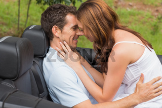Young couple feeling romantic in back seat