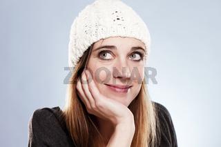 lächelnde frau mit wintermütze schaut nach oben