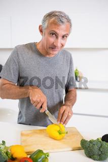 Happy man cutting a yellow pepper