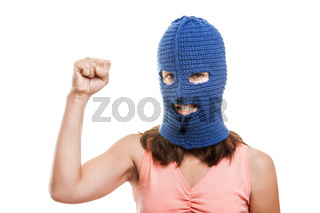 Woman in balaclava showing raised fist gesture