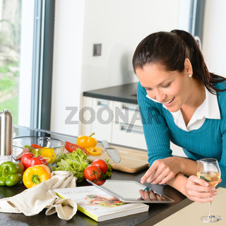Smiling woman searching recipe tablet kitchen vegetables
