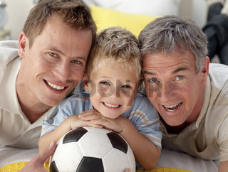Portrait of smiling son, father and grandfather on floor