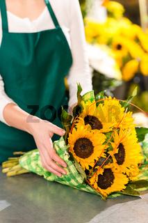Florist preparing sunflowers bouquet flower shop assistant