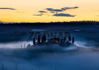 Tuscany farmhouse in morning mist with yellow skies, Val d'Orcia, Italy