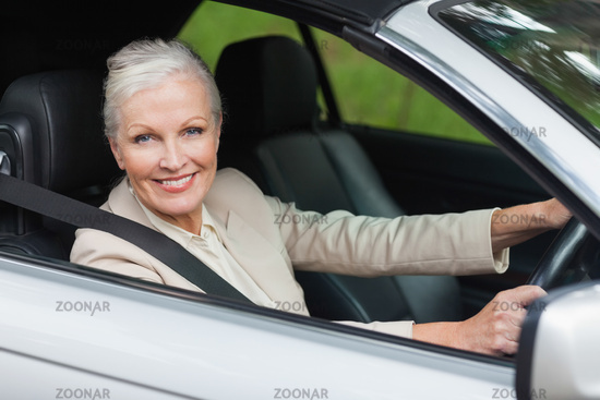 Cheerful businesswoman driving classy car