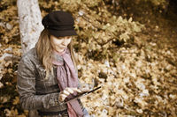 Woman with Digital Tablet in autumn forest