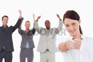 Businesswoman with cheering colleagues behind her giving thumb up