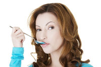 Portrait of woman with spoon in her mouth