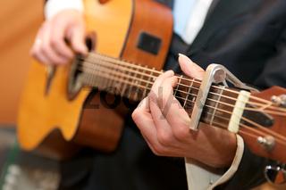 Musician playing a guitar, close-up photo