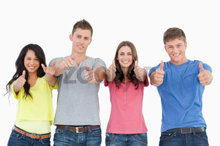 Four people standing beside each other give thumbs up