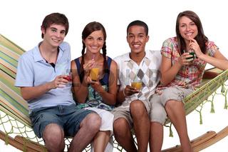 A bunch of friends enjoying cocktails on a hammock.
