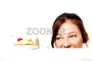 Girl hiding behind the desk and looking at the cake.