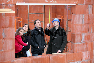 family and contractor on construction site