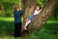 little boy photographing girl in the park on tree