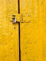 Padlock on an old yellow door