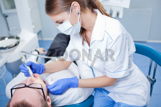 A young female dentist working in her office.