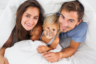 Family smiling under the duvet on the bed