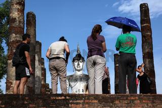 Touristen vor einer Buddha Figur  im Wat Mahathat Tempel in der Tempelanlage von Alt-Sukhothai in der Provinz Sukhothai im Norden von Thailand in Suedostasien.