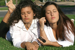 teens students relaxing on campus listening to music sharing earphones and personal stereo