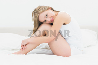 Portrait of smiling woman sitting in bed