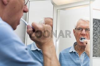 Senior man in mirror brushing his teeth