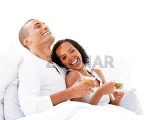 Joyful couple drinking a cup of tea lying on their bed