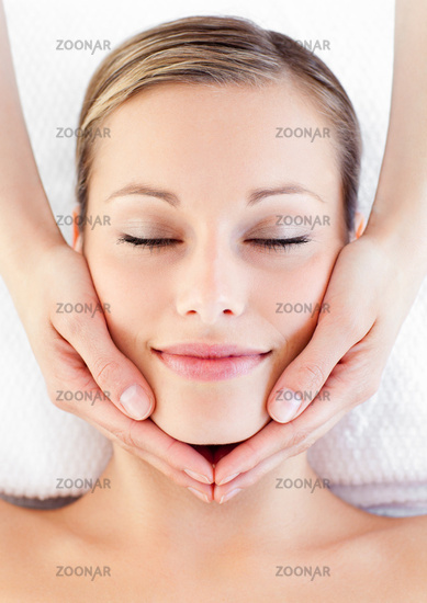 Young caucasian woman receiving a head massage in a spa centre