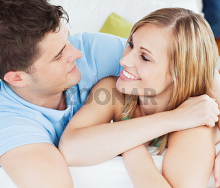 Portrait of a cute couple looking at each other relaxing on the sofa