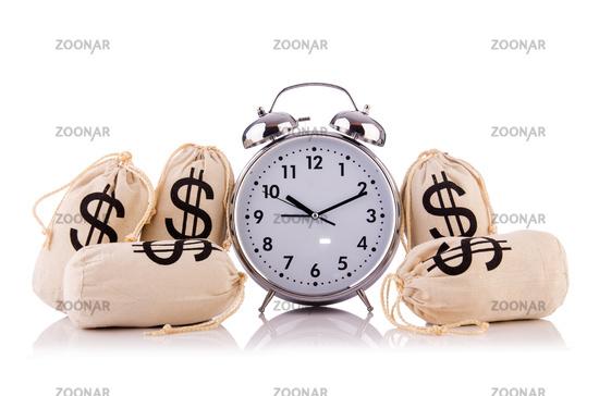 Sacks of money and alarm clock on white