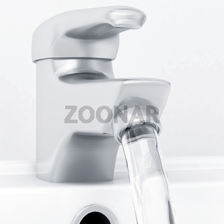 ceramic white washing sink with a modern faucet and flowing water