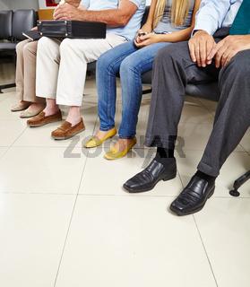 Gruppe von Patienten sitzt im Wartezimmer