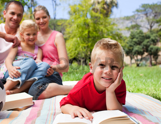 Smiling little boy reading lying on the grass while having a picnic with his family