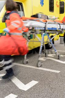 Blurry hurrying paramedics running with gurney