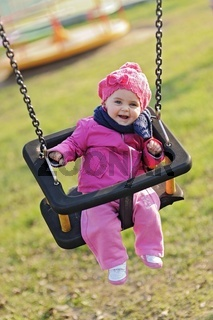 Happy baby playing with the swing