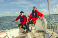 Two men in red jacket standing on the stern of a s
