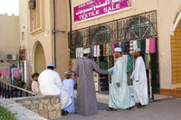 Omani men in Dishdash dress at a textile shop