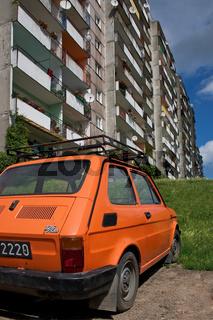 Oranges Auto im grauen Plattenbau
