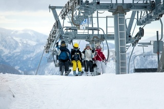 Skiers getting out the chair lift