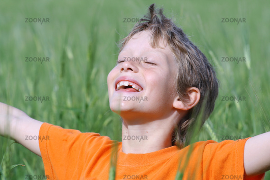 happy smiling child arms outstretched eyes closed