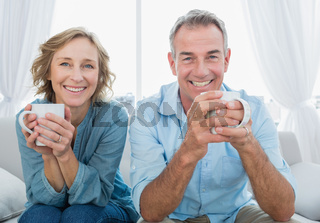 Smiling middle aged couple sitting on the couch having coffee