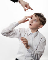 Boy rubs a forehead after blow. Looks upwards